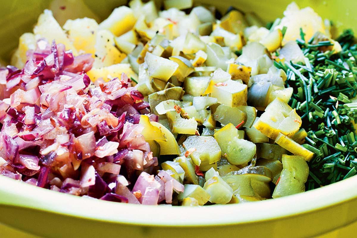 Die (vorgekochten) Kartoffeln und die sauren Gurken in Stücke schneiden. Zwiebeln und Knoblauch würfeln und glasig anbraten. Anschließend mit 500 ml Brühe, Essig und gehacktem Schnittlauch in einer Schale vermischen. Mit Chili, Salz und Pfeffer abschmecken und eine Stunde in den Kühlschrank stellen, damit der Salat gut durchziehen kann. Foto: Artur Jagiello