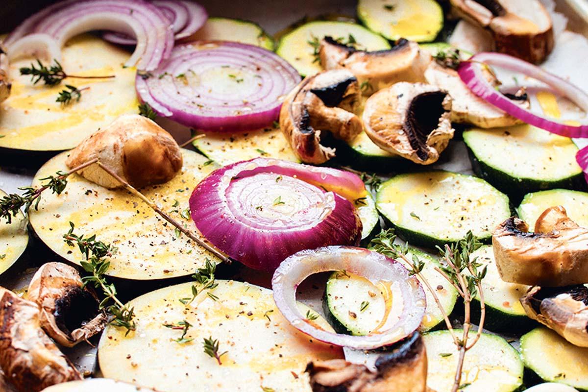 Aubergine, Zucchini, Zwiebel und Champignons in dicke Scheiben schneiden und auf dem Backblech verteilen. Mit grobem Meersalz, Pfeffer, frischem Thymian und Olivenöl würzen. Bei 200°C im Ofen 20 Minuten lang backen. Foto: Artur Jagiello