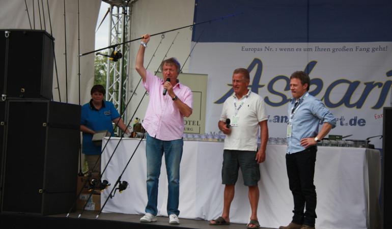 Zum Ersten, zum Zweiten, zum Dritten...Die Botschafter der Royal Fishing Kinderhilfe, Schauspieler Axel Pape, Eishockeytrainer Hans Zach und Entertainer Werner Schulze-Erdel (von rechts) helfen Petra Krichel von Shimano die Karpfen-Kombo zu versteigern. G. Bradler