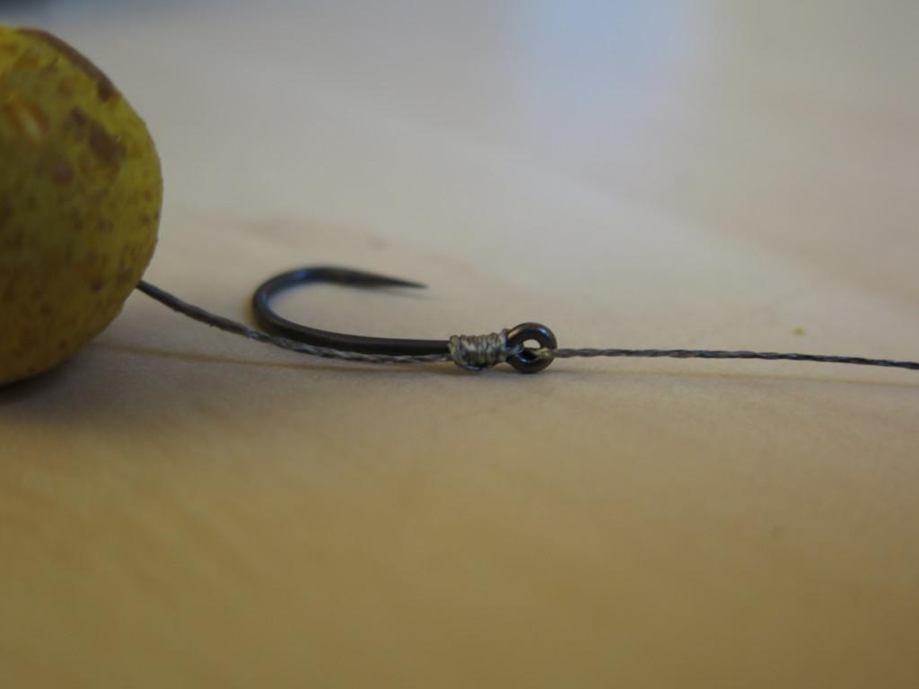 In dem nächsten Schritt beginnt man mit den Wicklungen, die das Vorfach und den Haken verbinden. Jeder Haken hat eine Seite bei dem der Guss endet, ihr startet von der anderen glatten Seite. So werden die Wickelungen noch sauberer. Umwickel den Haken ca. 6 bis 8 Mal. Anschließend das Schnurende von Innen nach Außen zurück durch das Öhr gefädelt. Tipp: Kleine spitze Haken drehen schneller und dringen besser in das Fischmaul ein. Zudem ist die Hebelwirkung geringer, sodass die Fische seltener im Drill ausschlitzen.