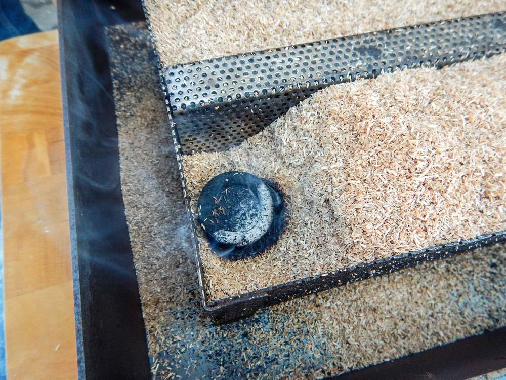 Das Kohlestück wird entzündet und in die Anfangsecke der Schnecke gegeben. Alternativ kann man auch einen Bunsenbrenner verwenden.