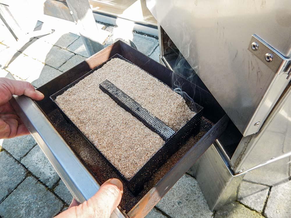 Das Kohlestück wird mit Räuchermehl bedeckt und dann wird die Schublade in den Ofen eingesetzt.