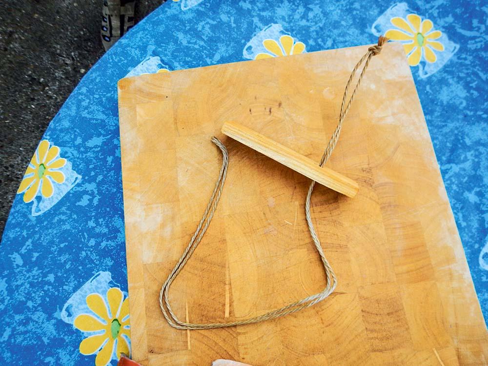 Aus einem kleinen Brettchen mit zwei Löchern und einer doppelt gelegten Kordel hat sich Peter eine spezielle Filet-Halterung gebaut. Natürlich können für das Kalträuchern auch Räucherhaken verwendet werden.