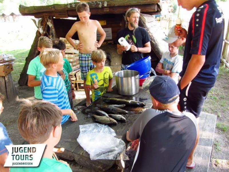 Mithilfe eines Betreuers wird der frisch gefangene Fisch von den Kinder für die Küche zubereitet. Foto: Jugendtours