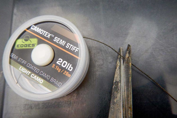 Zunächst trennt man mit einer scharfen Schere etwa 15 bis 20 Zentimeter des ummantelten Vorfachmaterials ab.