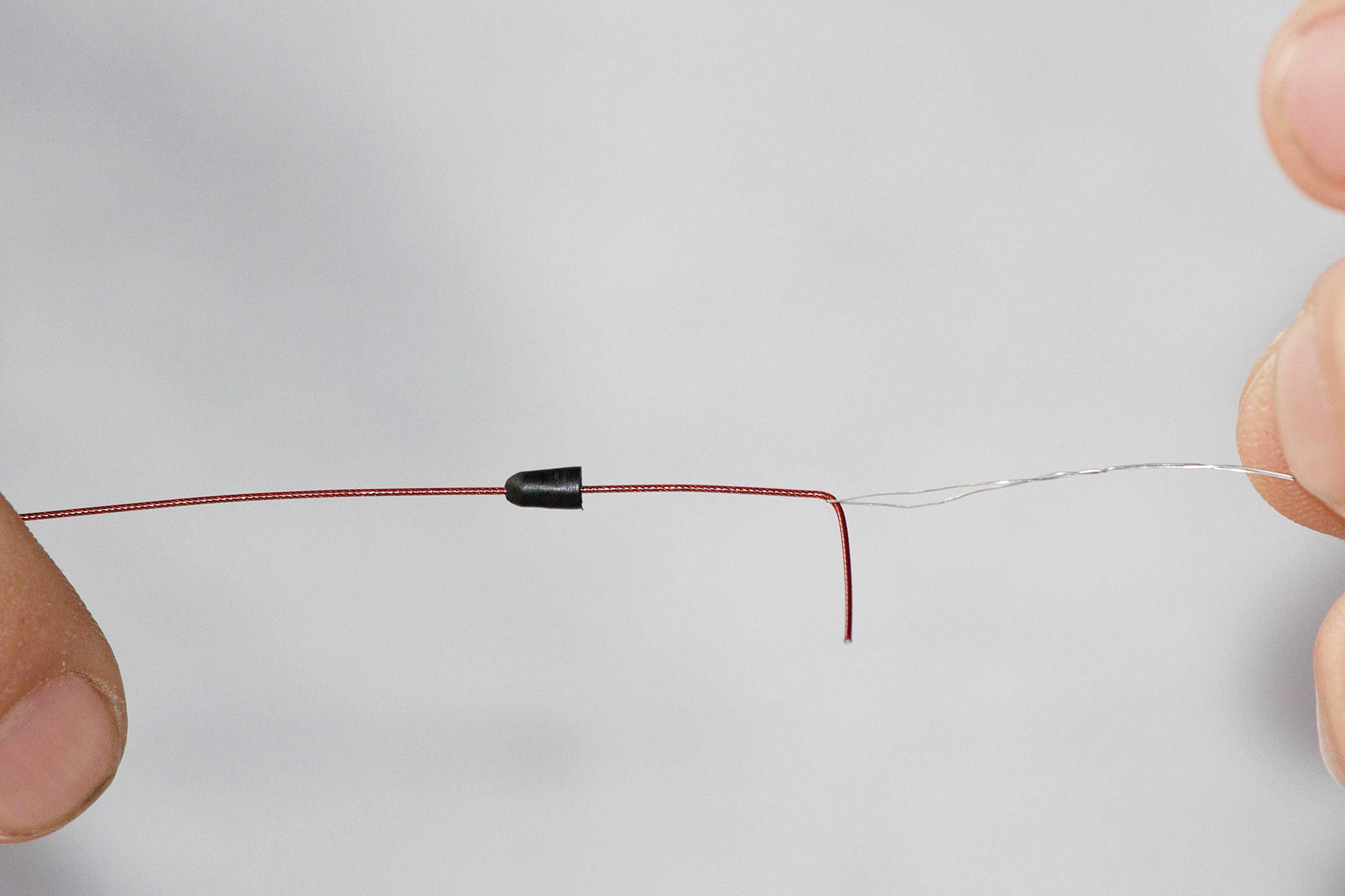 Als erstes zieht man den Schnurstopper mit ein wenig Kraft auf den weichen Stahldraht.