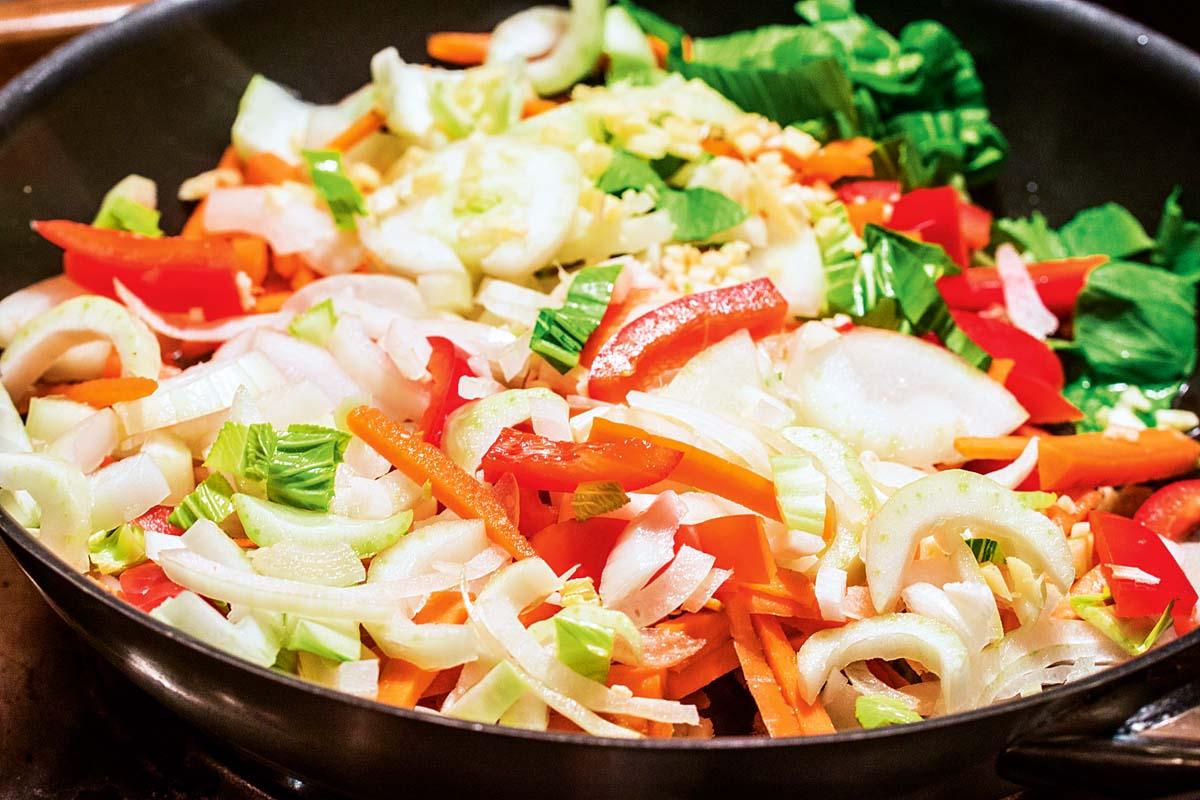 """Wir beginnen mit dem Gemüse. Pak Choi, Karotten, Paprika und Zwiebeln schneiden und in der Pfanne anschwitzen. Ein Teelöffel braunen Zucker hinzufügen, umrühren und mit einem Glas Wasser ablöschen. Danach ein Esslöffel Currypaste oder Pulver unter das Gemüse mischen. Mit Soja- und Fischsoße abschmecken und köcheln lassen. Für den nötigen """"Kick"""" sorgt eine scharfe Chili. Foto: A. Jagiello"""