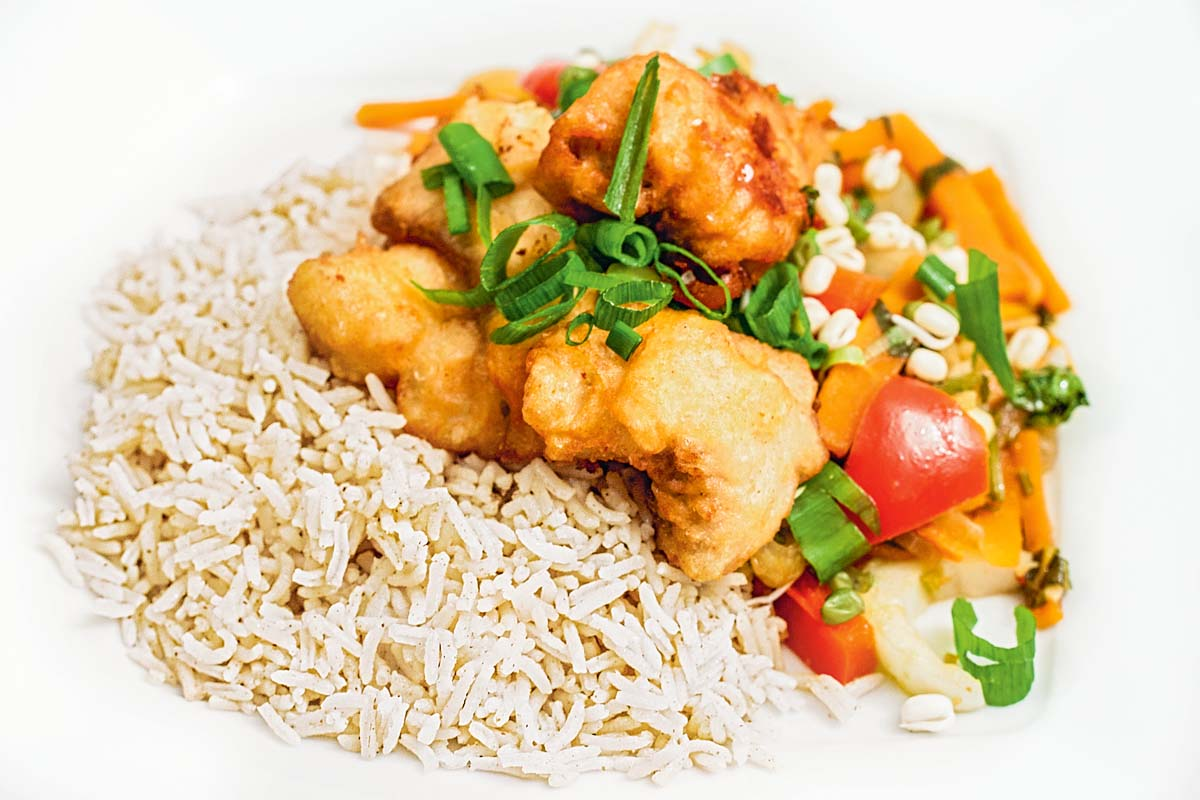 Serviert wird das Dorschfilet im Tempurateig mit Reis und Asiagemüse. Mit Frühlingszwiebeln und Mungobohnen garnieren und das leckere Gericht genießen. Guten Appetit!. Foto: A. Jagiello