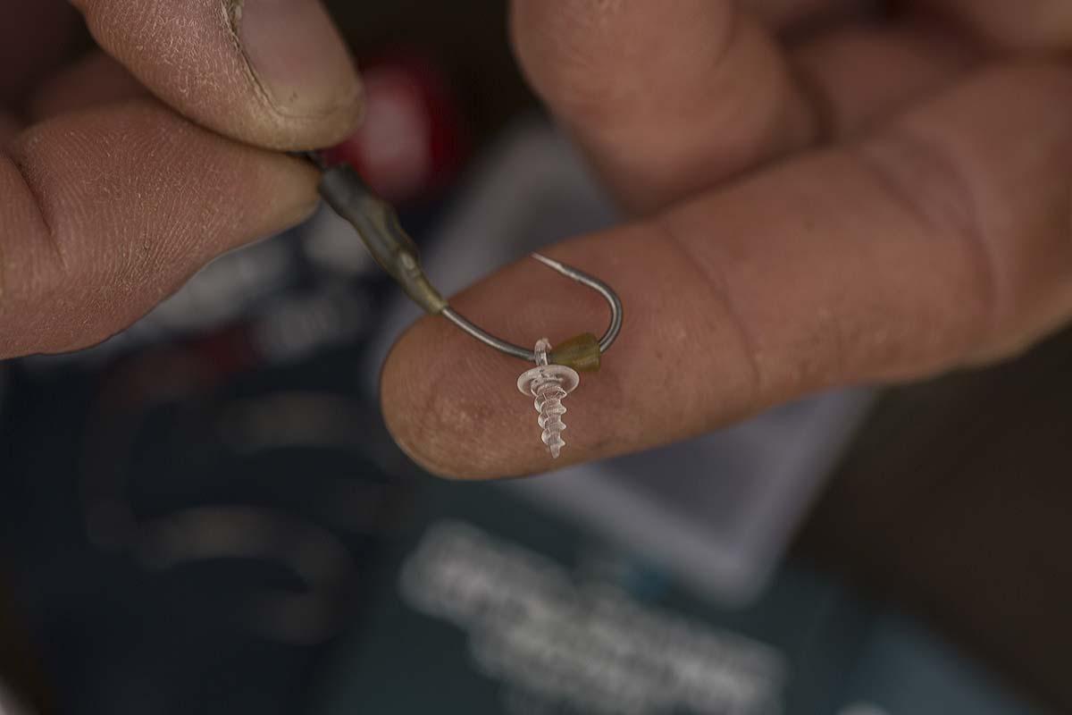 Eine Plastic-Bait-Screw und anschließend ein Hook-Bead, welches die Bait-Screw sichert, werden auf dem Haken platziert. Foto: karpfen/Max Hendry