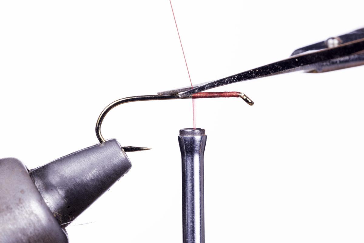 3 Nachdem Sie ca. 1/3 des Hakenschenkels umwickelt haben, können Sie das lose Ende des Fadens mit der scharfen Schere dicht am Hakenschenkel abschneiden. Foto: Harald Bayler