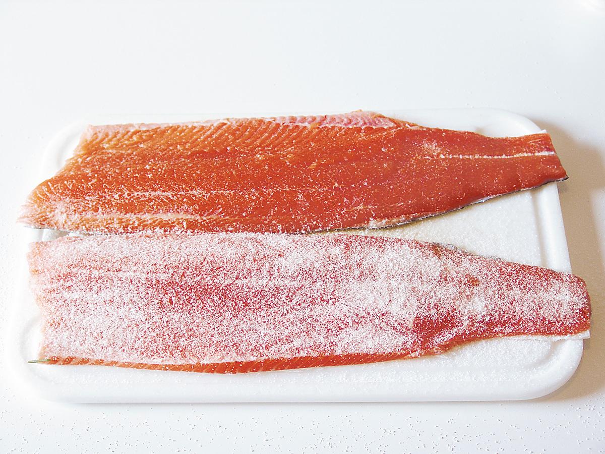 Die beiden Filets werden, Rücken an Rücken, mit der Hautseite nach unten auf ein Küchenbrett gelegt und gleichmäßig dünn mit Meersalz bestrichen. Dann kommen die Filets für ca. eine Stunde in den Kühlschrank. Nach der kleinen Pause wird eine der beiden Filethälften noch einmal kräftiger mit Meersalz bestreut. Richtwert: Streuen Sie einfach so viel Salz drauf, dass das Weiß des Salzes die rote Farbe des Fleisches fast vollständig überdeckt. Foto: BLINKER