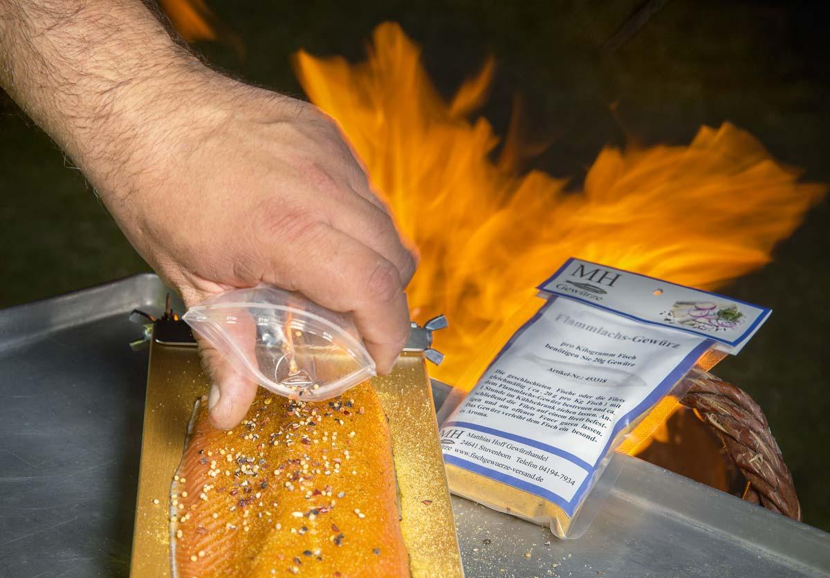 Zuerst wird das Filet mit der Hautseite auf das Brett gelegt und mit Flammlachs-Gewürz bestreut. Danach gibt man noch einige ganze Pfefferkörner auf das Filet. Diese geben dem Fisch die besondere Note.