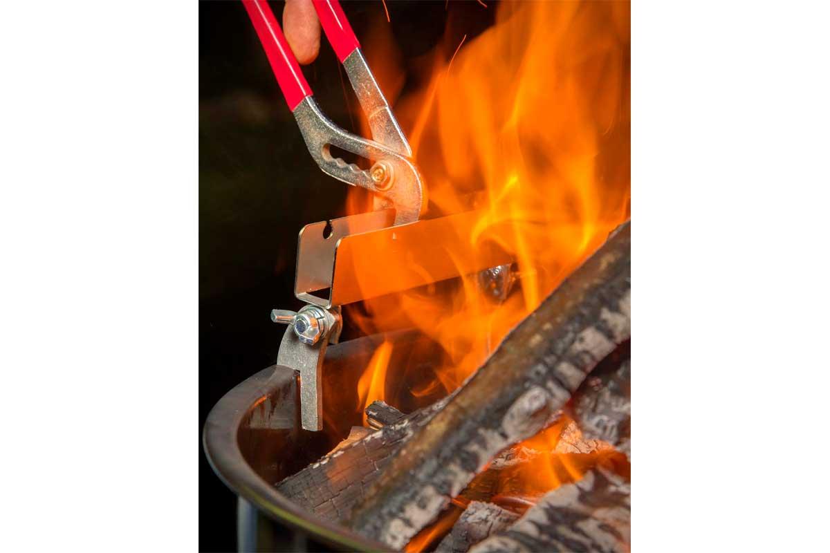 Als Nächstes befestigt man den Bretthalter an der Feuerschale. Er wird einfach angeschraubt. Damit man sich dabei nicht die Finger verbrennt, nimmt man dazu am besten eine Zange.