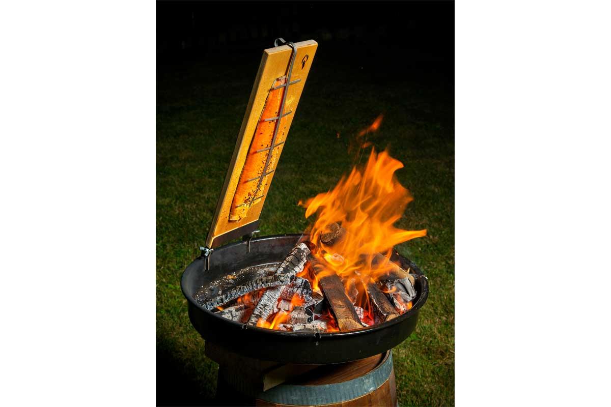 Das Flammbrett wird nun im 70 Grad-Winkel zum Feuer ausgerichtet. Dabei ist darauf zu achten, dass sich zwischen Flammen und Fisch ca. 20 Zentimeter Abstand befinden.