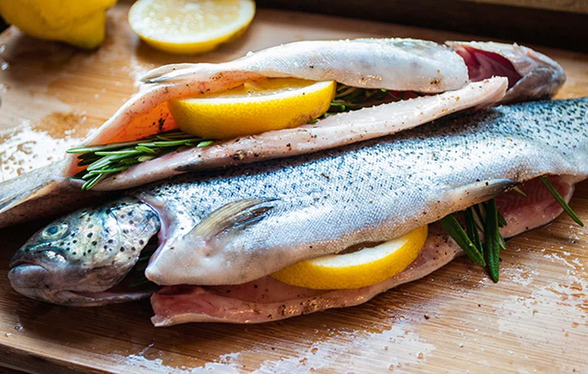 Die Forellen säubern, von beiden Seiten mit Salz und frisch gemahlenem Pfeffer würzen. In den Bauch Rosmarin und eine halbe Zitronenscheibe füllen. Foto: A. Jagiello