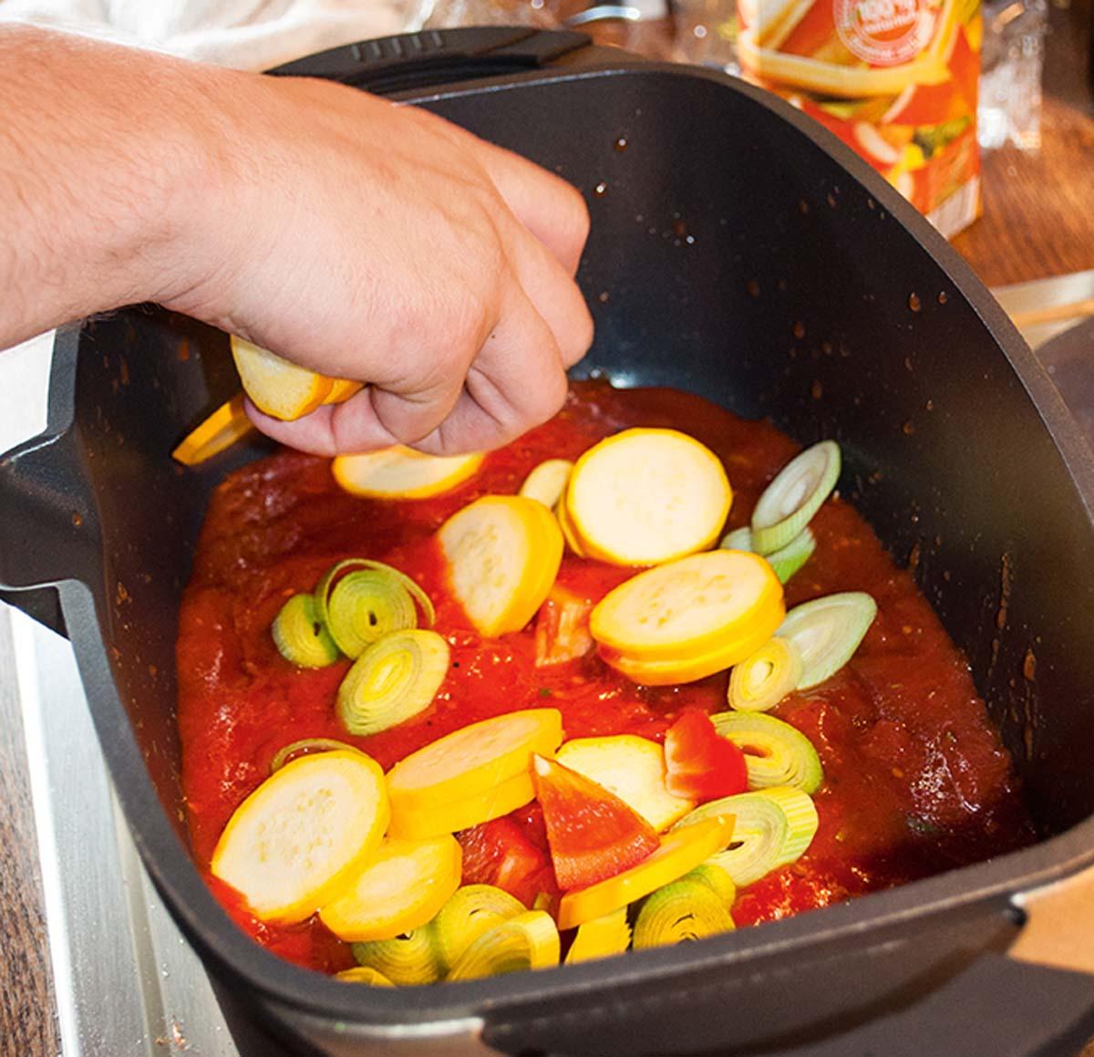 Das geschnittene Gemüse kommt nun zusammen mit der Tomatensoße in einen tiefen Bräter. Das Gemüse und die Soße müssen gut miteinander vermischt werden. Den Backofen auf 200 Grad vorheizen. Foto: A. Jagiello