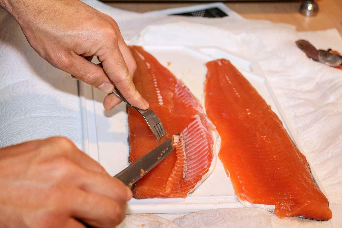 Die Forellen filetieren und parieren. Hierzu werden die Flossensäume und Gräten der Fische sorgfältig abgeschnitten. Mit ein wenig Übung, der Hilfe einer Gabel und einem scharfen Messer geht das schnell und einfach.