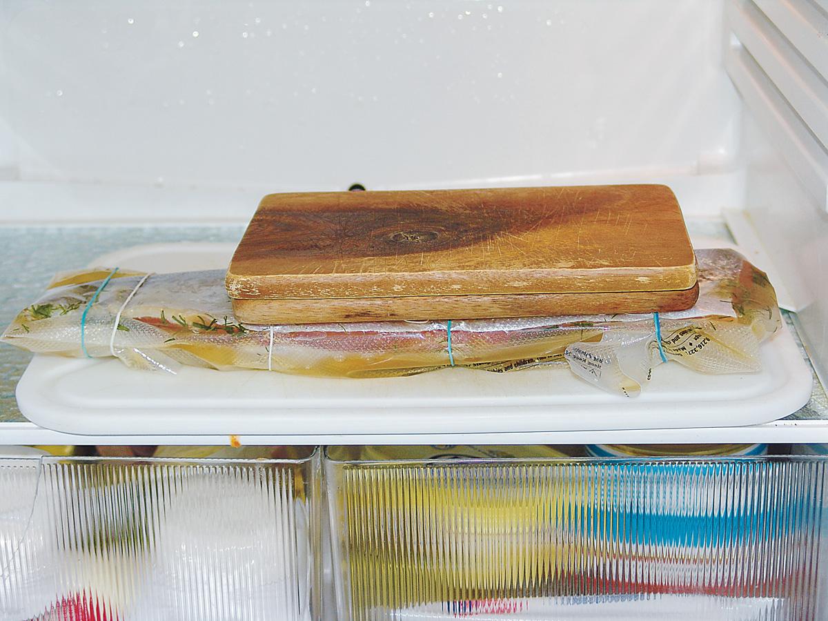 Das gesalzene und gezuckerte Filet wird nun auf das dick belegte Filet geklappt, genau so, wie wir es auch bei einem Sandwich machen! Jetzt kommt ein Trick, der den gesamten Reifevorgang sehr sauber gestaltet: Der Fisch wird zusammengeklappt in feste, lebensmittelechte Folie eingeschlossen und beschwert. Unbedingt ganz fest einwickeln, damit keine Flüssigkeit austreten kann. Profis benutzen für das Einschweißen ein Vakuumier-Gerät mit einer starken Pumpe. Die gesamte Luft wird aus dem Folienbeutel abgesaugt. So sind die Filets ständig unter Druck, was zur Reifung sehr wichtig ist. Foto: BLINKER