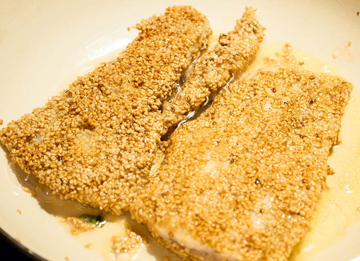Den panierten Zander von beiden Seiten braten, bis die Sesamkruste eine goldbraune Farbe annimmt. Danach den Fisch mit etwas Salz und Pfeffer würzen.