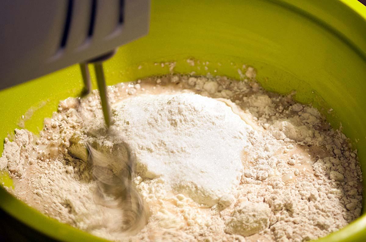 Nun die Hefe und 300 ml Milch mit dem Mehl vermischen und anschließend gut durchkneten. Am einfachsten geht dies mit einem Rührgerät und einem Knetaufsatz. Anschließend den Teig mit einem Küchentuch bedecken und für 45 Minuten an einem warmen Ort gehen lassen. In dieser Zeit können wir uns der Soße und den Beilagen widmen.