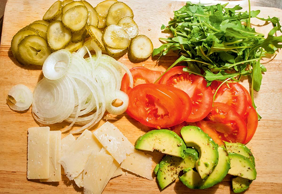 Als Beilagen benötigen wir Tomaten, Zwiebeln, saure Gurken, Rucola, Parmesan und mit etwas Zitronensaft und Salz angemachte Avocado., die später mit in den Fischburger kommen.