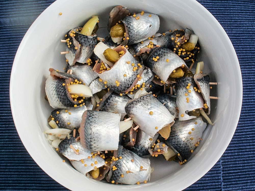 Die Rollmöpse in eine Schüssel legen, Zwiebelscheiben, Pfeffer- und Pimentkörner, Lorbeerblätter und Senfkörner daraufgeben.