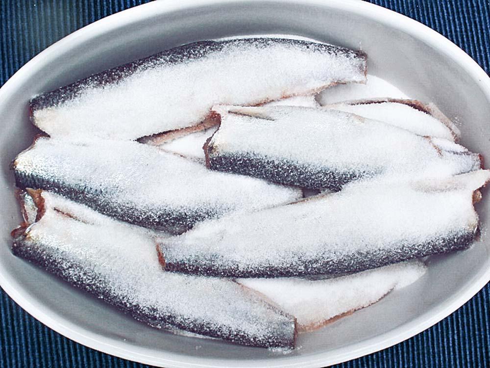 Eine Schicht Salz in eine große Schüssel geben und die Heringe dicht nebeneinander darauf legen. Dann wieder eine Schicht Salz, eine Schicht Heringe und so weiter. Die obersten Lage dick mit Salz bestreuen. Etwa 24 Stunden gekühlt stehen lassen.