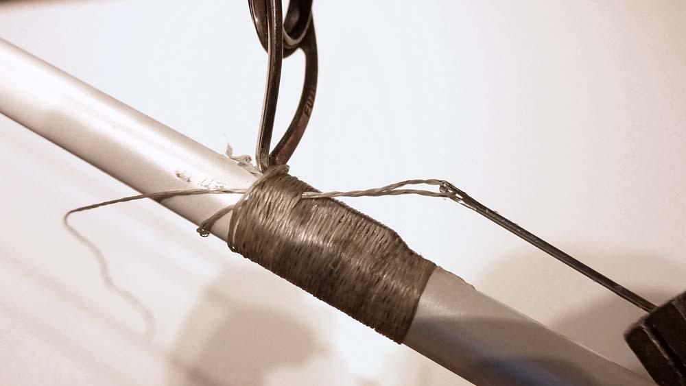 Anschließend zieht man die Nadel mit Hilfe einer Zange aus den Wicklungen und somit das Ende des Fadens unter das Wickelgarn.