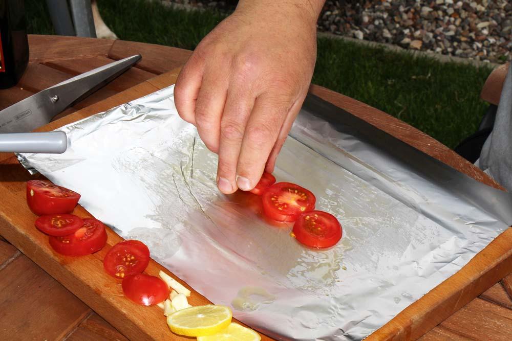 Tomatenscheiben als erste Lage auf die Folie legen.