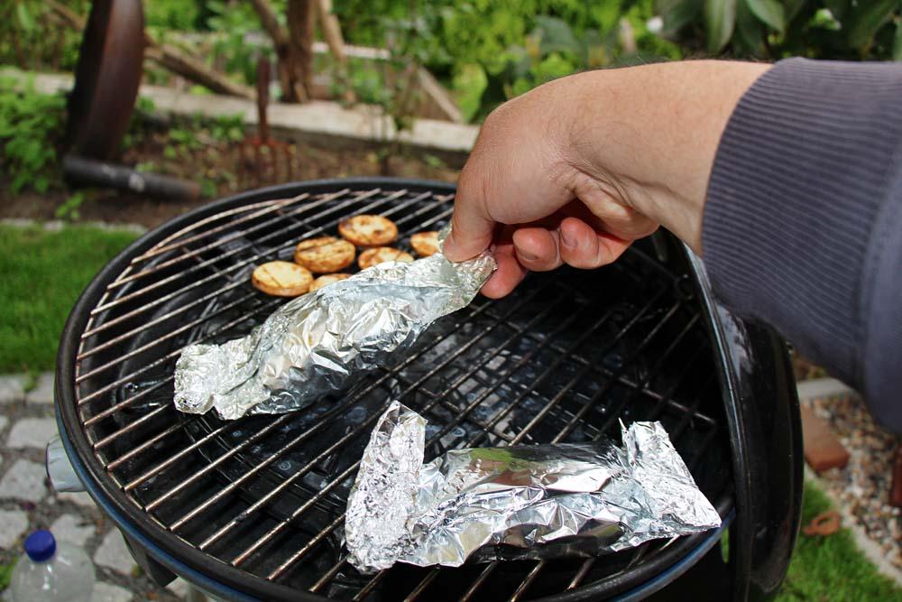 Den Fisch in Alufolie vom Grill nehmen und öffnen.