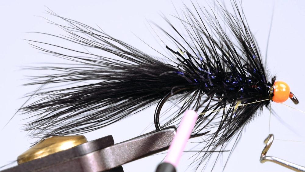 10. Nun winden Sie die lange Hechelfeder. Eine Hechelklemme ist dabei hilfreich. Streichen Sie dabei nach jeder Windung die Fibern nach hinten.