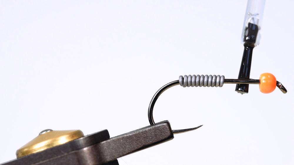 3. Nach dem Aufbringen der Wicklung wird wasserfester Klebstoff zwischen der Wicklung und der Tungsten-Perle auf dem Hakenschenkel aufgetragen …