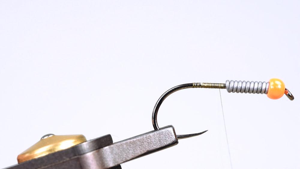 5. Mit dem Bindefaden den Hakenschenkel dicht an dicht überwickeln. So wird ein Fundament geschaffen, damit sich der Körper der Fliege später nicht dreht.