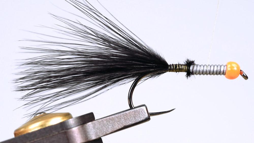6. Schneiden Sie seitlich vom Stamm die weichen Hecheln einer Marabou-Feder ab und formen Sie auf diesen ein kleines Bündel, das Sie als Schwanz einbinden.
