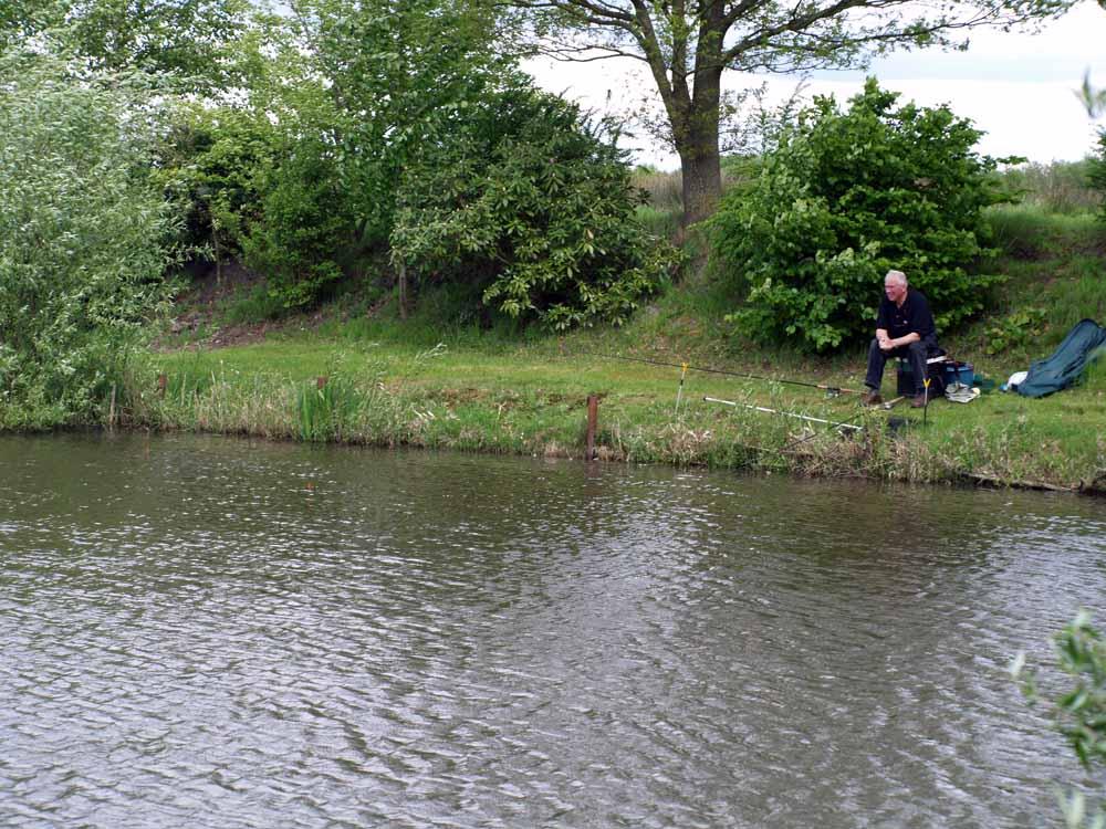 Wolf-Rüdiger beim Ansitz an einem Moorsee in der Nähe der holländischen Grenze. Zwei Ruten sind ausgelegt. Da der Wind direkt auf das Ufer steht und Nahrung anspült, müssten sich hier auch die Fische aufhalten.