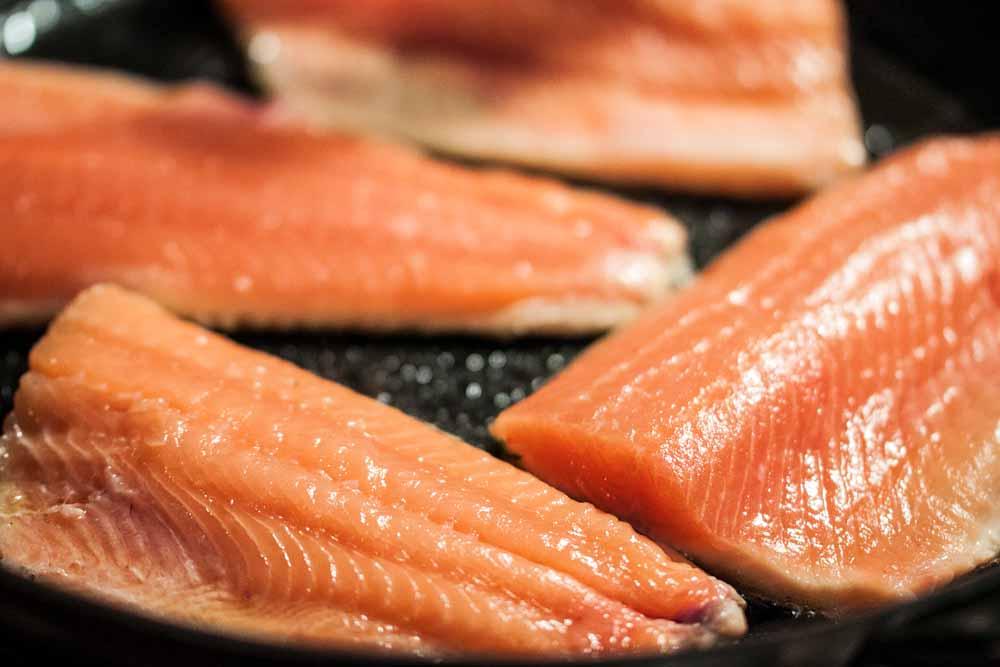 Die Lachsforelle auf der Hautseite braten und nicht mehr wenden! Bei der Dicke zieht der Fisch auch auf nur einer Seite in der Pfanne durch. Sollte er dicker sein, dann nur zum Schluss kurz wenden.