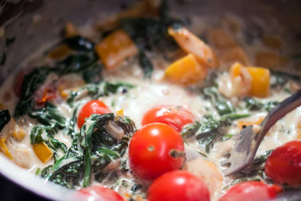 Den Blattspinat bei mittlerer Hitze langsam zu einer cremigen Masse kochen. Am Ende die Tomaten hinzufügen und diese aufstechen, damit ihr Saft sich mit dem Rest der Flüssigkeit vermischt. Ganz zum Schluss den Parmesan reinreiben und Frühlingszwiebeln unterrühren.