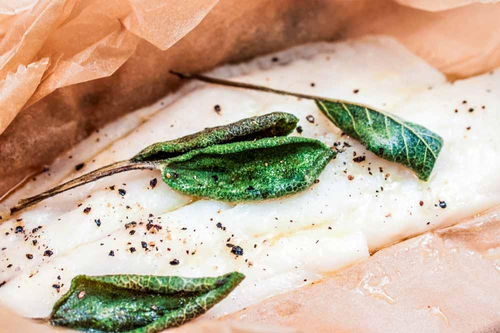 Das Backpapier vorsichtig öffnen, da sich einiges an Flüssigkeit gebildet hat. Diese Buttersoße kommt am Ende über den Fisch, sobald er in der Suppe ist.