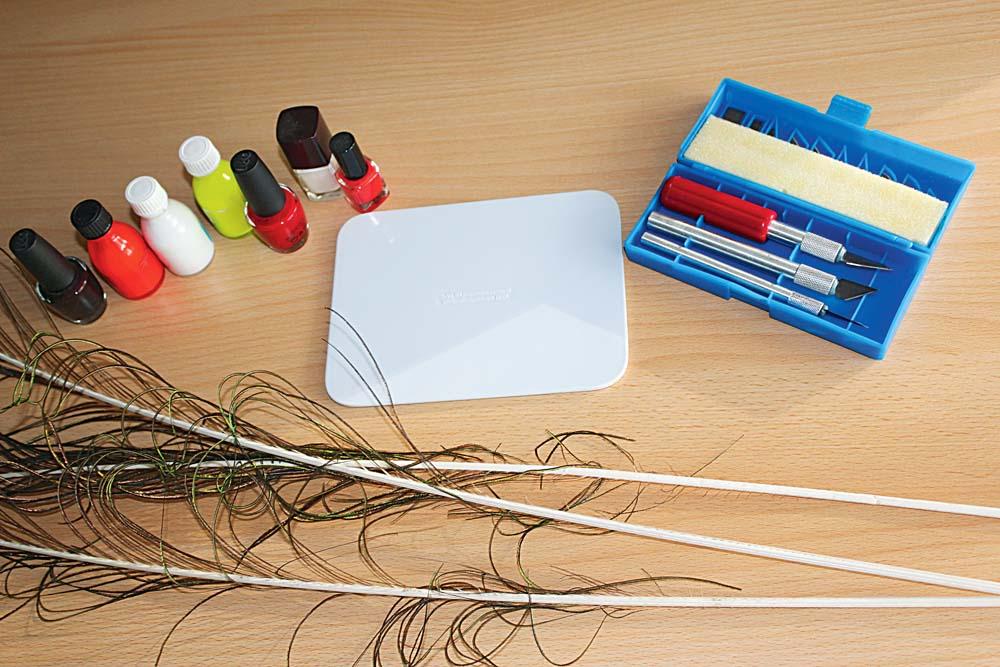 Für den Eigenbau der Federkiele benötigt man folgendes: Pfauenfedern (1), scharfe Cuttermesser (2), Grundierung (3), Posen- oder Nagellack (4).