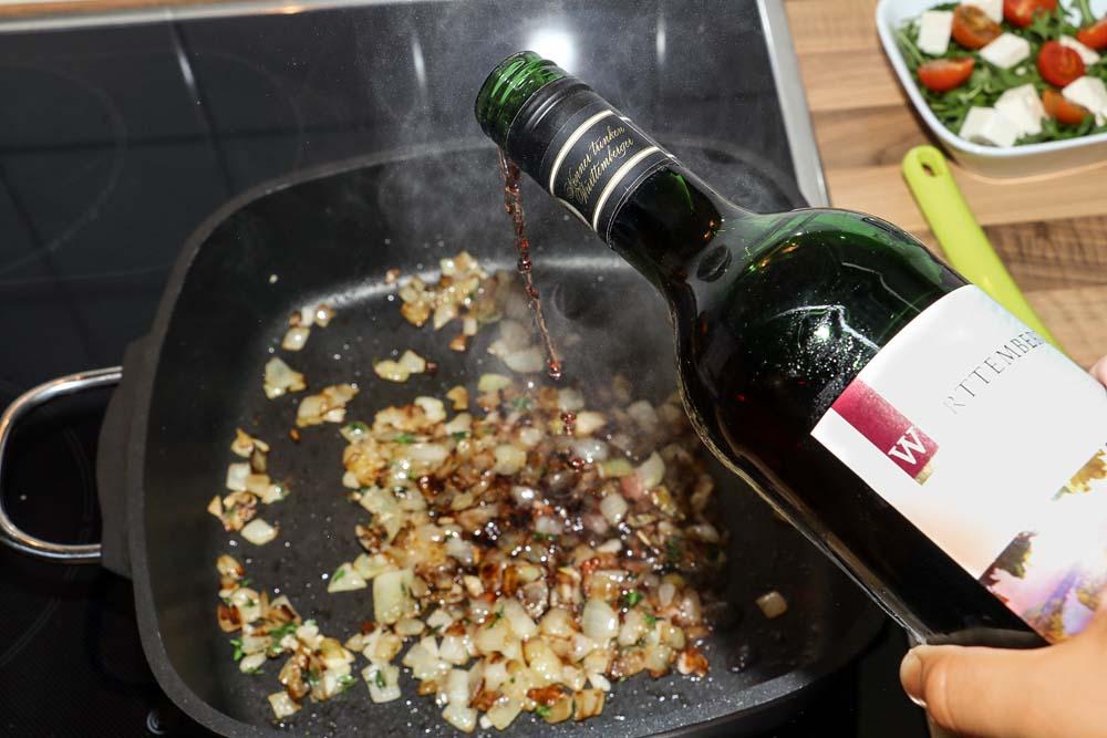 Den Rotwein hinzugeben und die Temperatur erhöhen.