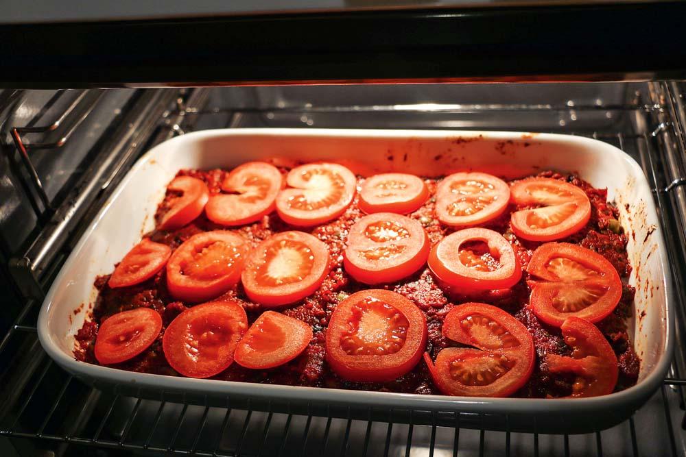 Tomatenscheiben auf dem Auflauf verteilen und bei ungefähr 180 Grad für ca. 25 Minuten in den Backofen schieben.