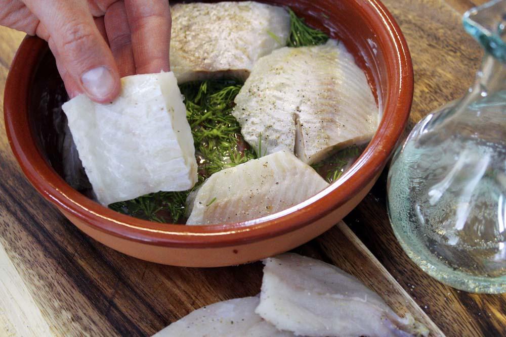 Die Auflaufform mit Butter einpinseln. Anschließend den Wein sowie den zerkleinerten Dill zugeben und die Fischfilets nun darin platzieren.