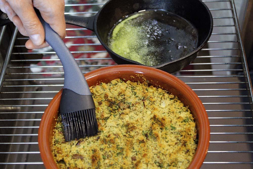 Nach der Hälfte der Garzeit am Rand der Auflaufform etwas Fischfond nachgießen und ein bisschen geschmolzene Butter über die Kruste pinseln.