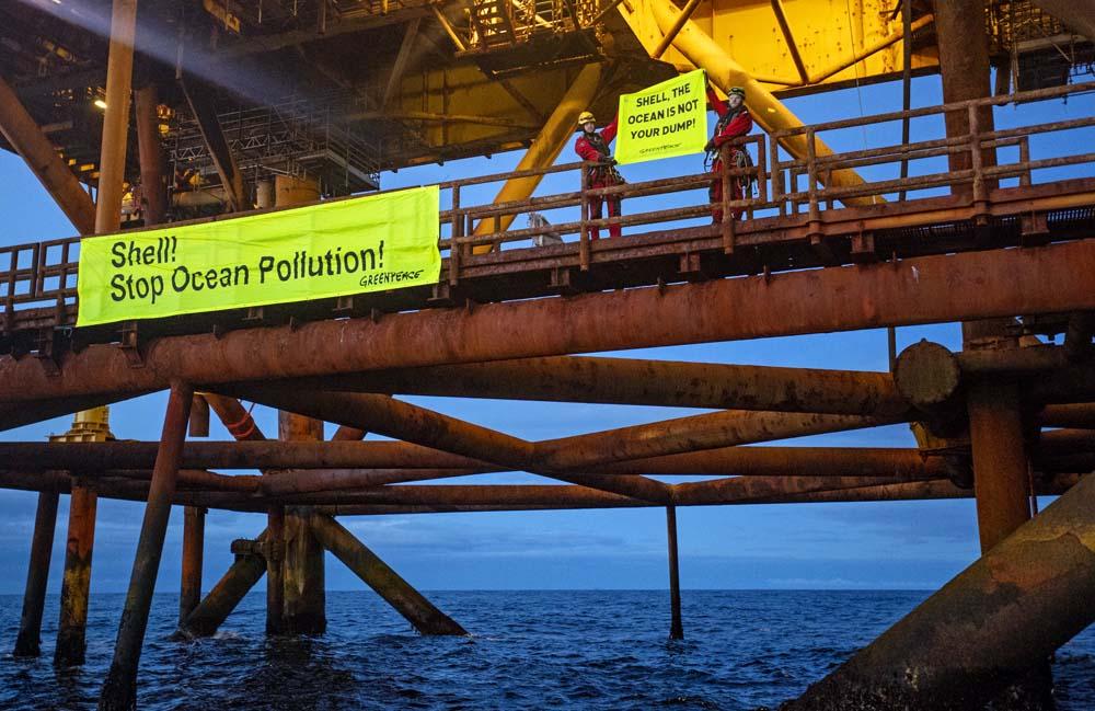 """Große Transparente mit den Aufschriften """"Shell, clean up your mess!"""" Und """"Stop Ocean Pollution"""" wurden an den alten Plattformen befestigt."""