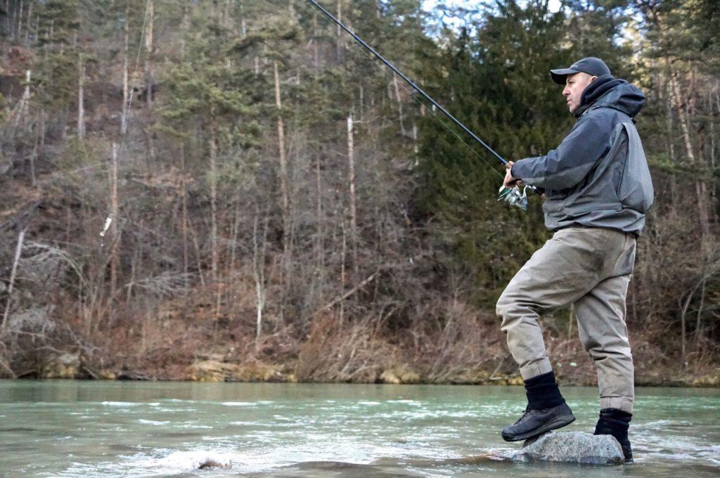 Beim Spinnfischen auf Huchen mit Wobbler oder Gummifisch muss man nicht tief waten. Dieser Experte zeigt, wie es geht: Er befischt das Flachwasser und hält dabei die Rutenspitze hoch. Dabei wird der Köder langsam eingeholt.