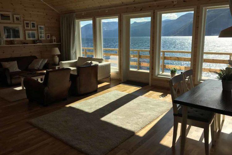 Die Sitzecke im Wohnzimmer lädt zum Entspannen ein. Wer möchte hier nicht gerne den Sonnenuntergang durch die große Fensterfront genießen? Foto: Borks