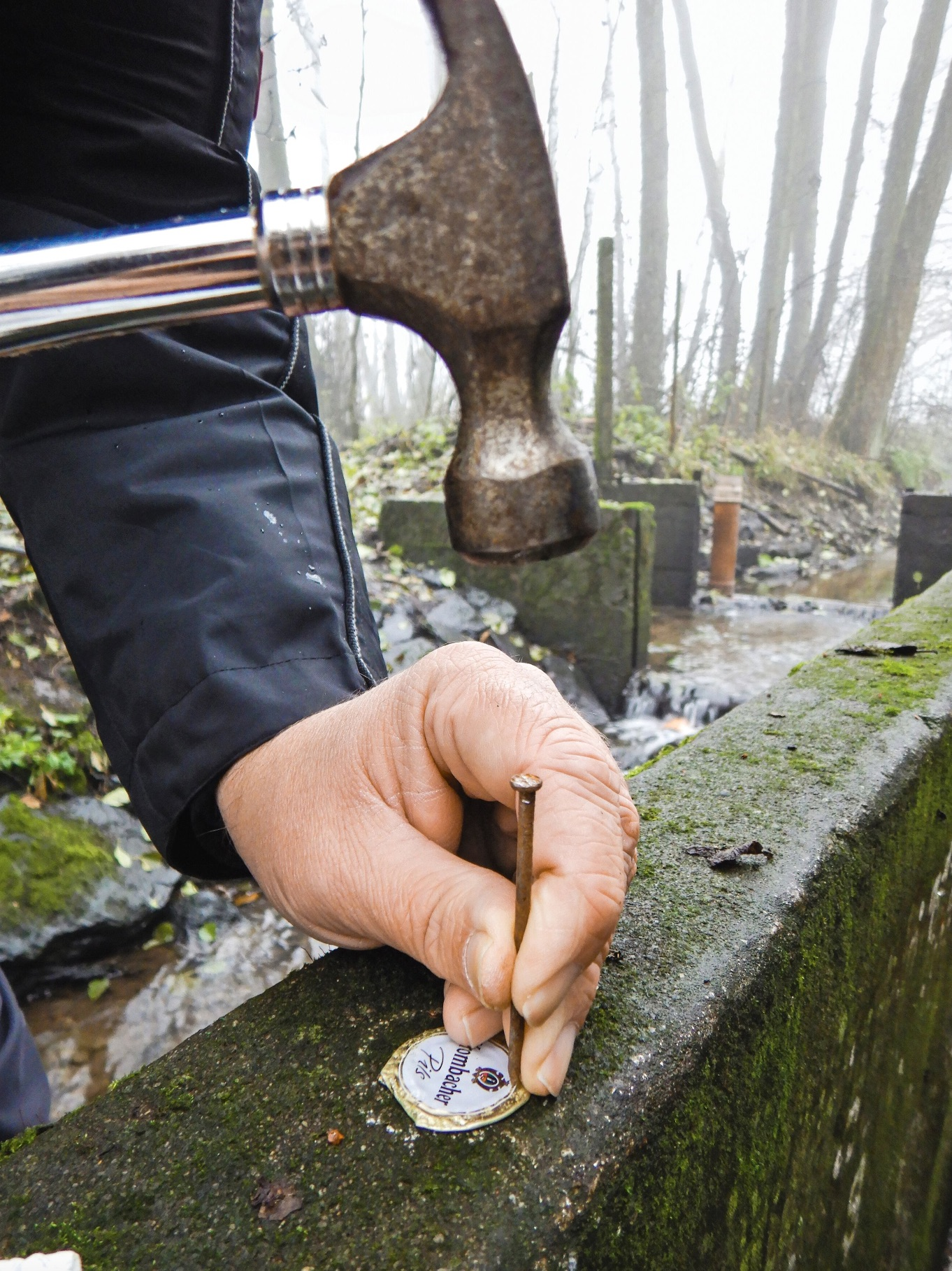 """Im nächsten Schritt werden mit einem Nagel Löcher in den Korken geschlagen. Das geht ebenfalls auf der Steinmauer. Wichtig: Die kleinen Löcher sollten so dicht wie möglich am Rand des Blechs liegen. Scharfe Kanten an den Löchern werden vorsichtig """"geplättet""""."""