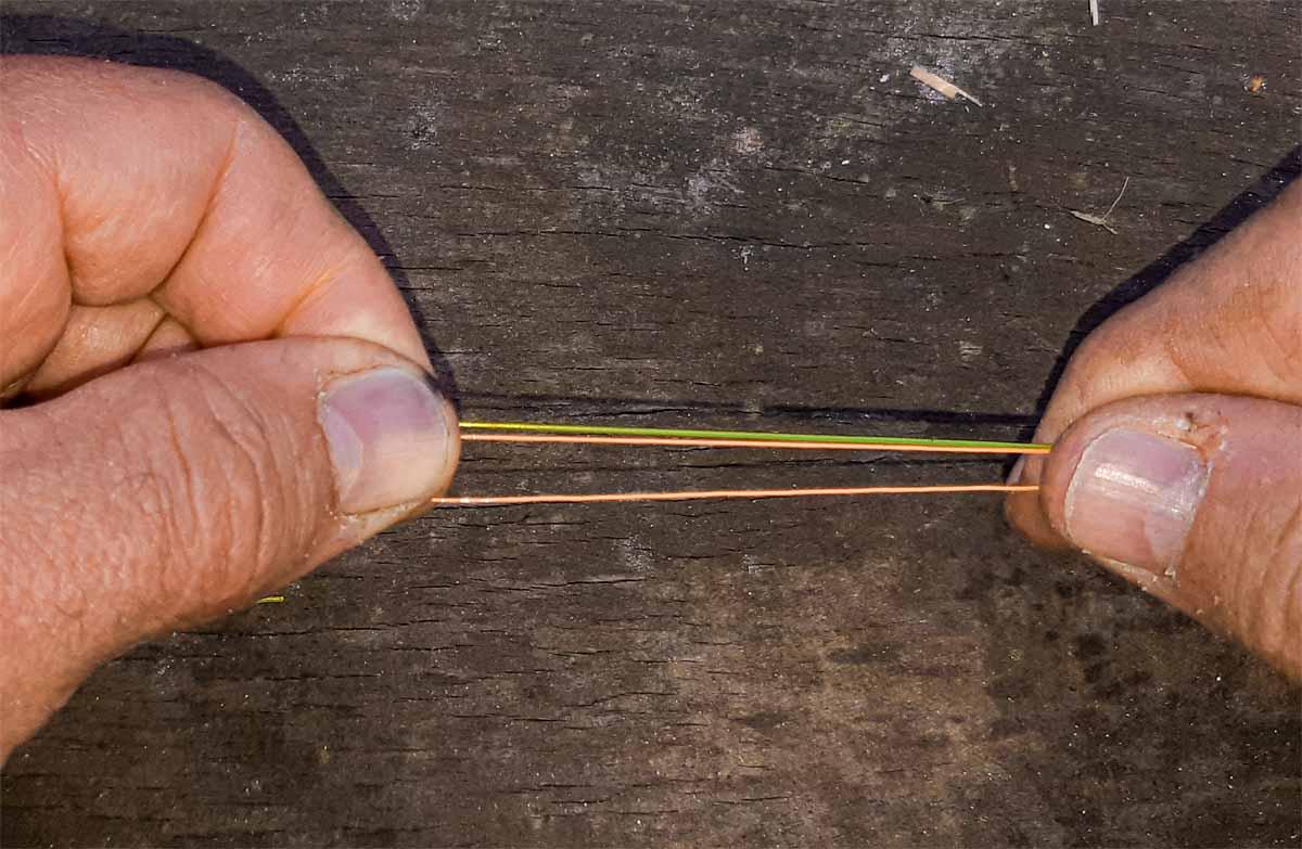 Den Stopperfaden stramm zur Angelschnur (gelb) legen und festhalten. Achtung: Stopperfaden und Angelschnur müssen parallel zueinander liegen und dürfen sich auch später nicht umeinander wickeln!
