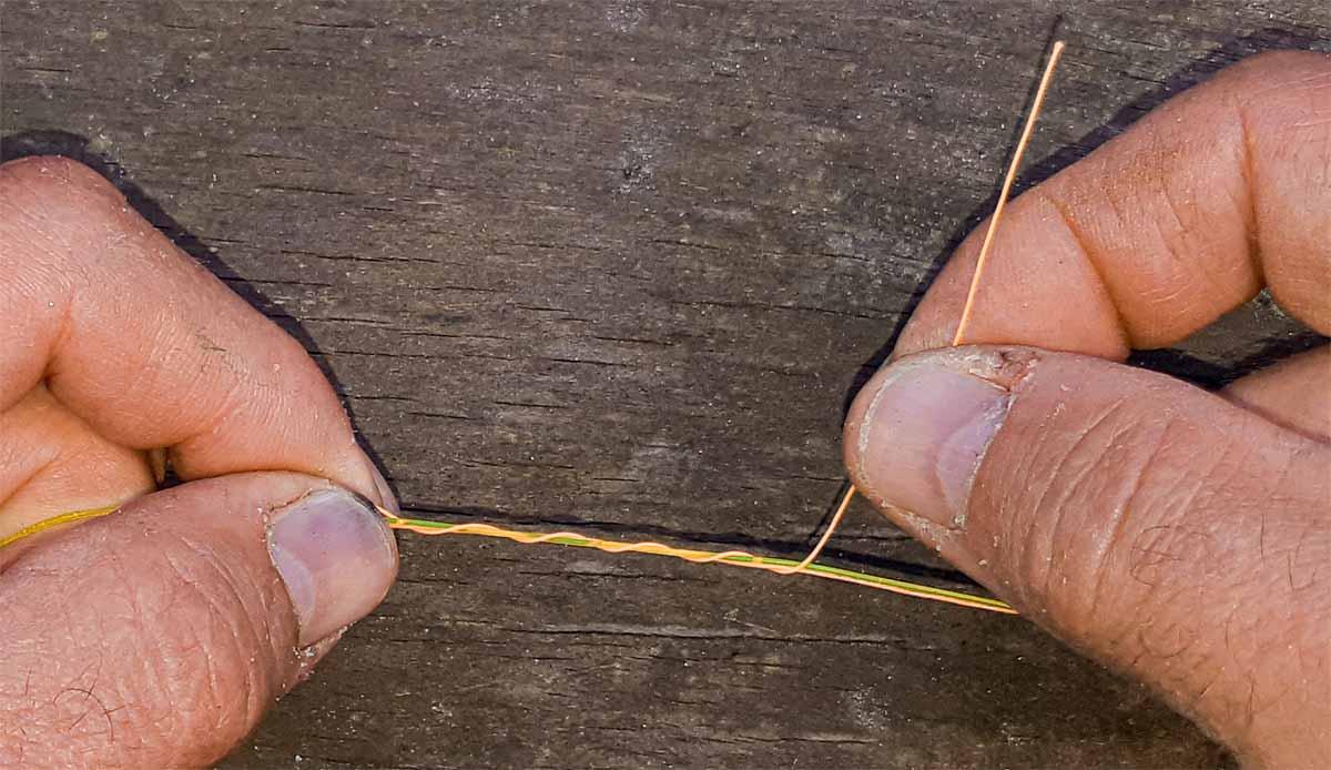 Jetzt das eine (kürzere) Ende des Stopperfadens um sich und die Angelschnur wickeln. Die Menge an Windungen bestimmt auch, wie dick der Knoten wird. Aber immer sollten es mindestens 5 Windungen sein.