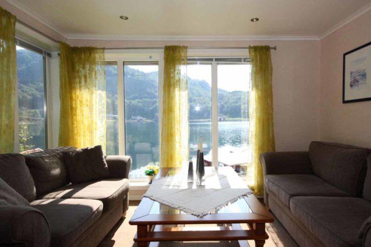 Dank der großen Fenster haben Sie auch vom Wohnzimmer aus einen grandiosen Blick auf das Wasser. Auch am Abend ist es die ideale Kulisse für ein gemütliches Beisammensein. Foto: Borks